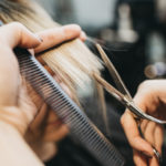 Close up of hairdresser cutting hair holding comb